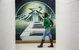 A NSU art student walks past a mural in the Hamm Fine Arts Building on Thursday, November 19, 2015. (Tigermoth Photo/Chris English)